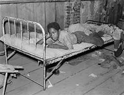 Russell Lee, Boy resting on bed in attic of sharecropper shack. New Madrid County, Missouri, 1938