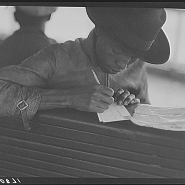 Migratory worker on the Norfolk-Cape Charles Ferry, writing a postcard home to his parents